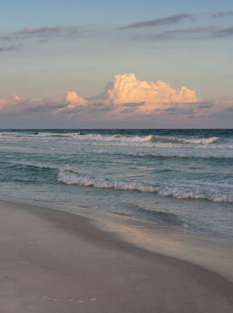 Just before dark at a beautiful Florida beach with crisp surf and puffy pink clouds. Stock Photo