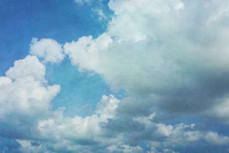 Blue sky with gathering cumulus clouds in shades of blue ranging from turqouise to cobalt blue, vintage light grunge texture. Good for backgrounds.