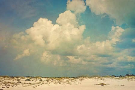 Toned and artistically grunge textured, vintage style landscape of puffy cumulus clouds over sand dunes and sea oats.