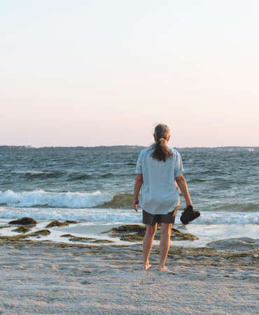 Back view of barefoot, middle aged woman on a seaweed laden beach looking out over the surf as the day dawns.
