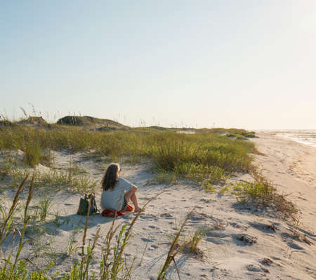 Seated woman in pristine sand dunes at Florida Gulf Coast beach looks out to sea as the sun rises.