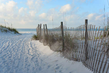 Sandy road through the dunes to the beach, bordered by twisting wooden sand fence in the very early morning. Stock Photo