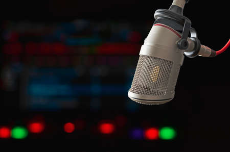 Professional microphone and sound waveform on screen Stock Photo