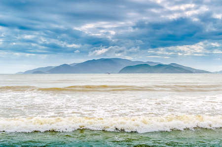 Island in the sea, waves and dramatic sky Stock Photo