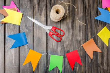 crafts: colorful paper flags on a string and scissors