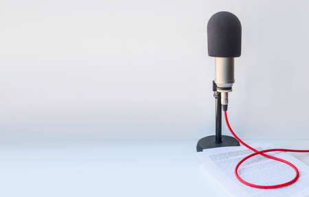 for podcasters: background with a professional microphone and sheets of paper