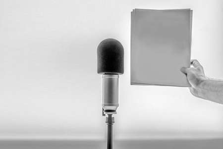 background: professional microphone, male hand holding a blank sheet of paper Standard-Bild