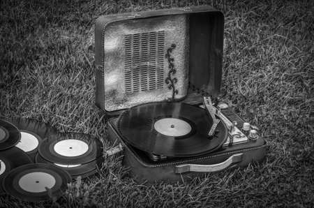 vintage portable turntable and vinyl records on the grass