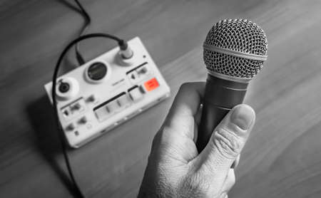 podcast interview: hand holding a microphone