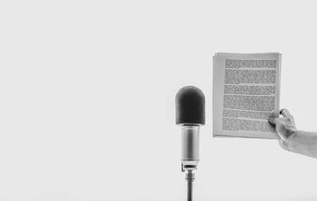 male hand holding a sheet of paper with text near microphone