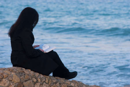 poems: Young long-haired woman in black trench coat reading book by the sea on a spring day