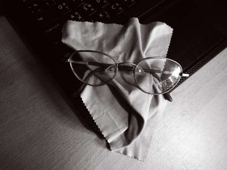 Eye glasses with cleaning cloth and laptop  photo