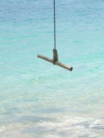 wood  swing  and blue sea photo