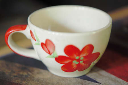 white cofee cup with red flower paint Stok Fotoğraf - 124728980