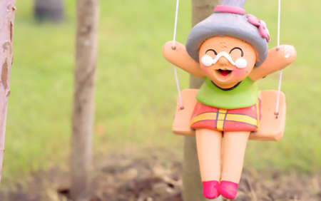 clay doll old woman smile  on swing
