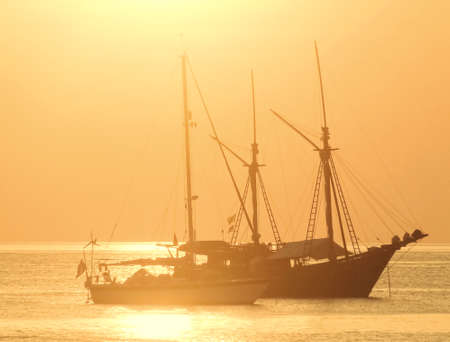 Golden sunset with boat in the sea  background Stock Photo