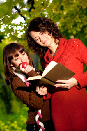 Beautiful smiling girls with book in park Stock Photo - 12034682