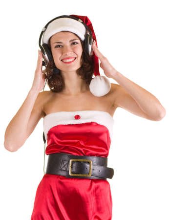 Beautiful young girl in Santa Claus clothes with headphones is listen to the music photo