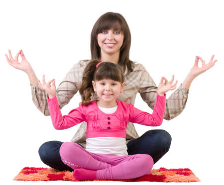 Happy family, young beautiful mother and her little daughter embracing in meditation