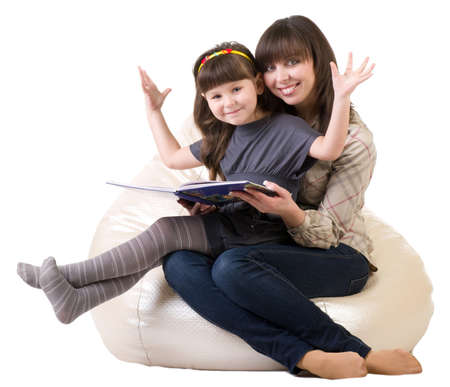 Mother and daughter reading a book on white background. photo