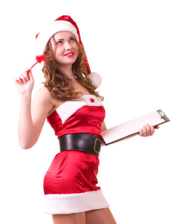 Beautiful young woman in Santa Claus clothes leaning on blank board on white background. photo