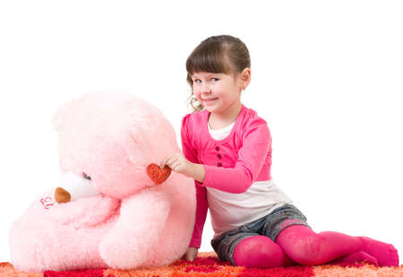 Cute little girl with pink bear on white background photo