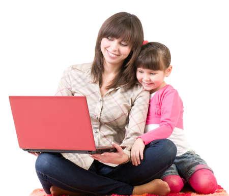madre soltera: Familia feliz, hermosa madre joven y su peque�a hija con la computadora port�til aislados en blanco