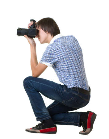 take action: Young man photographer doing photos by digital camera isolated on white background