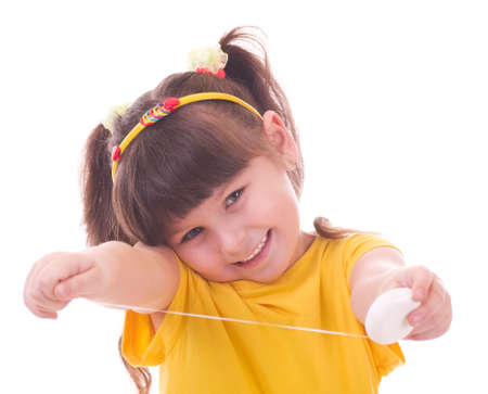 Beautiful little girl flossing her teeth on a white background