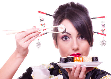 model fish: Young woman in Japanese kimono with chopsticks and sushi roll, isolated on white background.