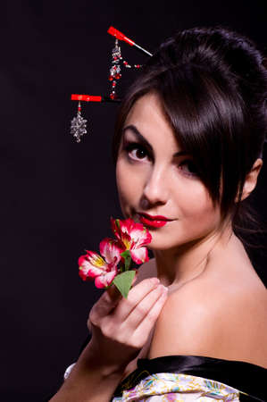 Beautiful young woman in Asian costume with red flowers on black background. photo