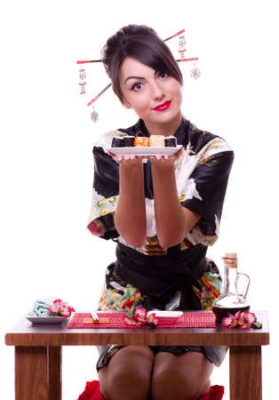 Young woman in Japanese kimono with chopsticks and sushi roll, isolated on white background.