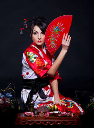 Beautiful young woman in Asian costume with red Asian fan