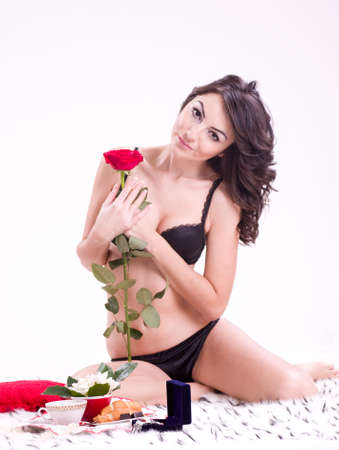 Beautiful young brunette woman in bed with rose on a Valentine photo