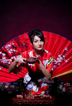Beautiful young woman in red Asian costume arranging Japanese tea ceremony photo