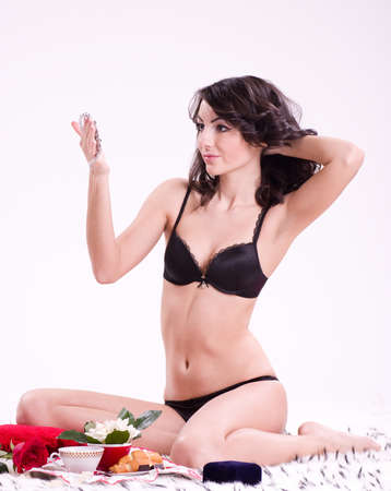 Beautiful young brunette woman in bed with gifts on a Valentine photo
