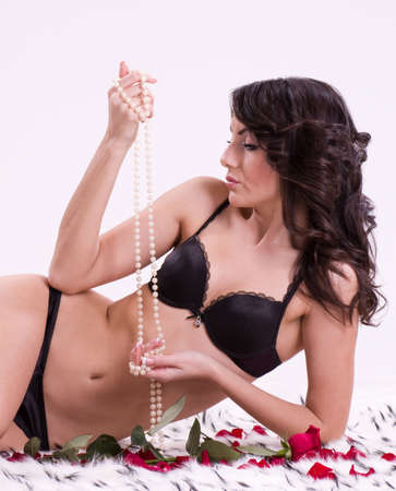 Sexy beautiful brunette girl with beads and pearls of rose photo