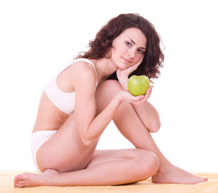 Beautiful young woman with green apple on white background photo