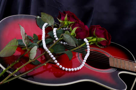 Beautiful red guitar with red rose on black background photo