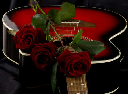 red roses: Beautiful red guitar with red rose on black background Stock Photo