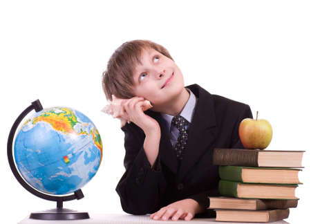 Little schoolboy looks at a globe with books and apple photo