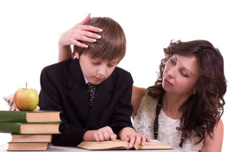 Little schoolboy with mother reading books isolated on a white background photo