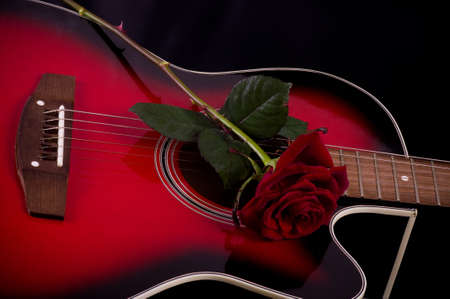 Beautiful red guitar with red rose on black background 스톡 콘텐츠