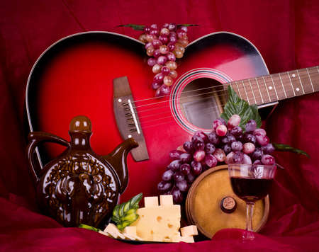 Beautiful composition with wine, grape, cheese and guitar on red background photo