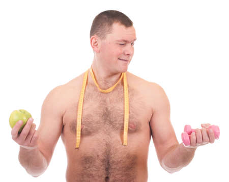 Young man with apple, dumbbells and measure photo