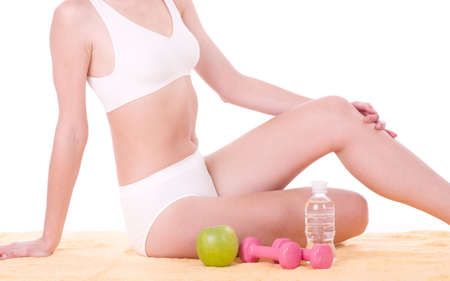 Beautiful young woman with apple, dumbbells and water photo
