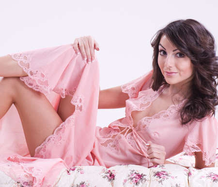 Sexy beautiful brunette girl in pink peignoir photo