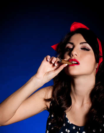 Vintage woman with cigar on dark background  Pin-up girl photo