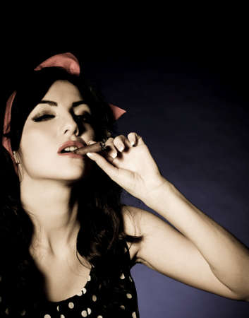 Vintage woman with cigar on dark background  Pin-up girl Stock Photo