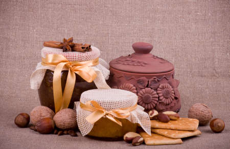 Tasty jam, cupcakes, clay pot and nuts on background photo